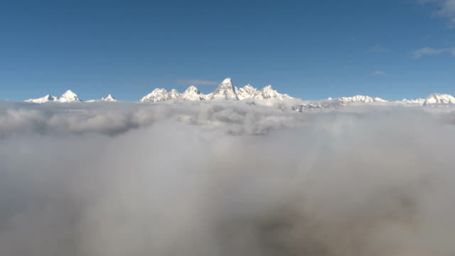 AERIAL: Majestic snowy Grand Teton mountain peaks disappearing in fog and clouds video