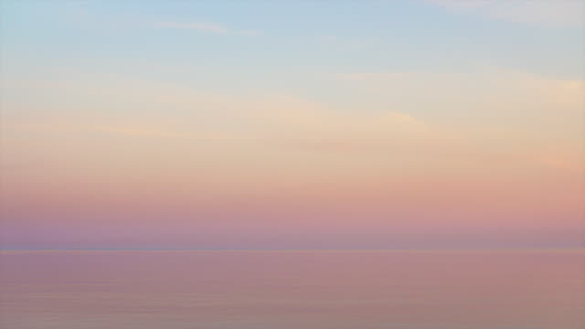 Majestic sunset in pastel tones over calm water. Looped seamless video. Majestic sunset in pastel tones over calm water, looped seamless video. pink color stock videos & royalty-free footage