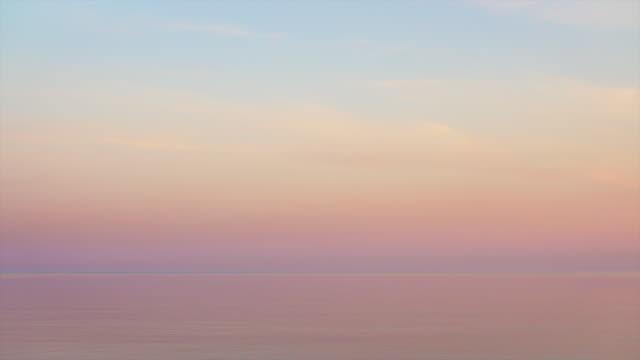 majestic sunset in pastel tones over calm water. looped seamless video. - różowy filmów i materiałów b-roll