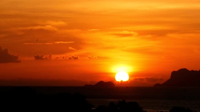 Majestic tropical orange summer timelapse sunset over sea with mountains silhouettes. Aerial view of dramatic twilight, golden cloudy sky over islands in ocean. Vivid dusk seascape natural background.