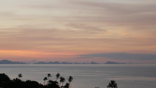 雄大な熱帯紫色の夏は、山のシルエットと海の上をタイムラプス日没。海の島々の上に劇的な夕暮れ、曇り空の空中ビュー。鮮やかな夕暮れの海の自然な背景 - サムイ島点の映像素材/bロール