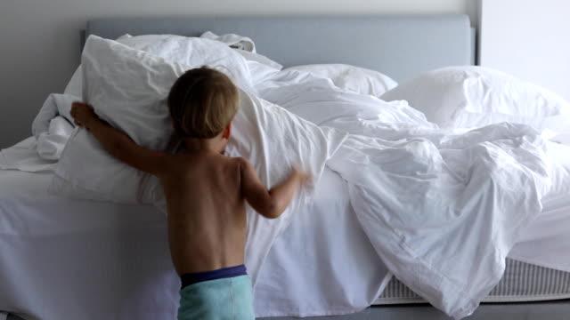 bir yatak, uyku modundan çıkarma sonra onun yatak odasında telafi çocuk yapmak - yapmak stok videoları ve detay görüntü çekimi