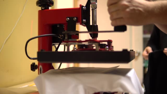 make a print on t-shirts. press presses the t-shirt and makes a picture on it. t-shirt printing, thermal printing - maglietta video stock e b–roll