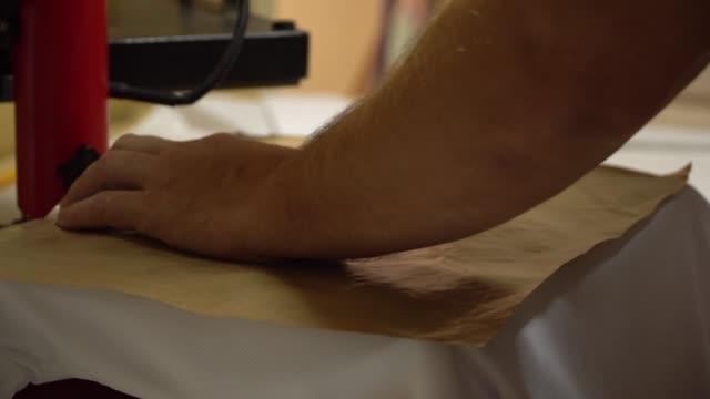 vídeos y material grabado en eventos de stock de hacer una impresión en camisetas. el operador coloca una camiseta debajo de la prensa, impone un papel impresión y prensas. impresión de camisetas, impresión térmica - moda playera