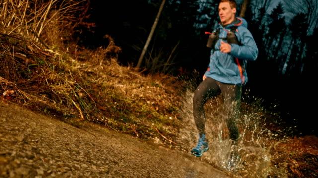 vidéos et rushes de slo mo faire runner traversant un ruisseau sous le soleil - évasion du réel