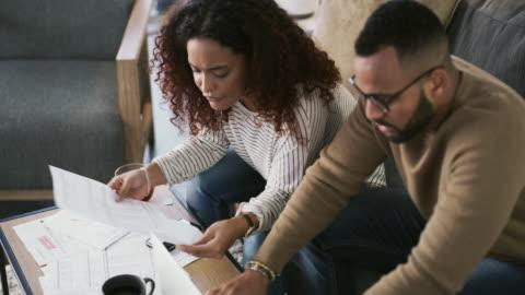 vidéos et rushes de assurez-vous de faire des opérations bancaires avec la banque qui vous aidera à grandir - jeune couple