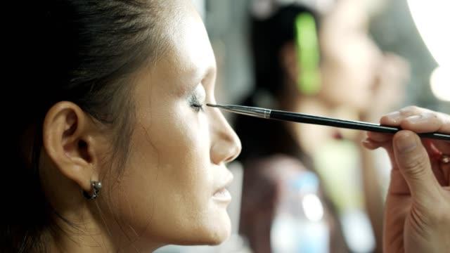 make up artist tillämpa eye ögonskugga pulver på vacker kvinna ansikte - makeup artist bildbanksvideor och videomaterial från bakom kulisserna