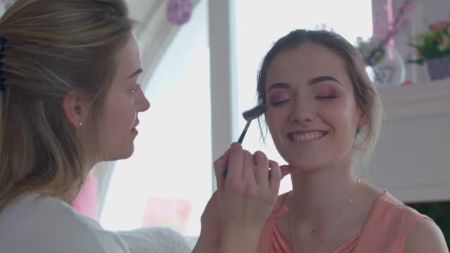 vidéos et rushes de maquilleur appliquant surligneur sur son modèle - fard à paupières