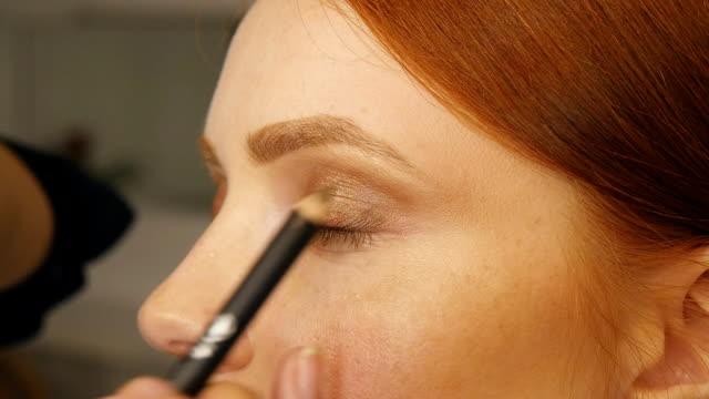 Make up artist at work, correcting eye lashes video