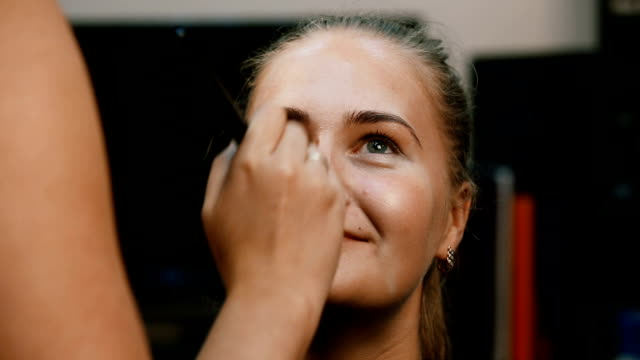 Make up artist doing professional make up of young woman video