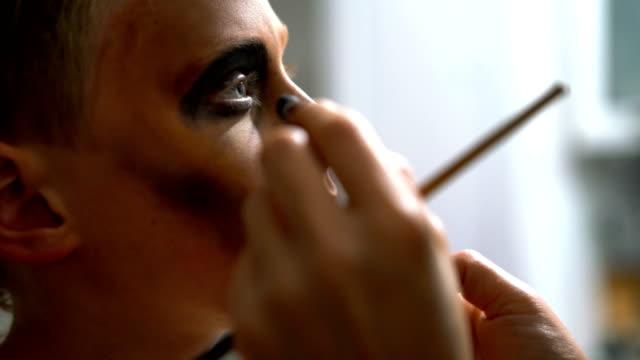 Make up artist working on a Halloween facial art on boy's face. 4K resolution video.