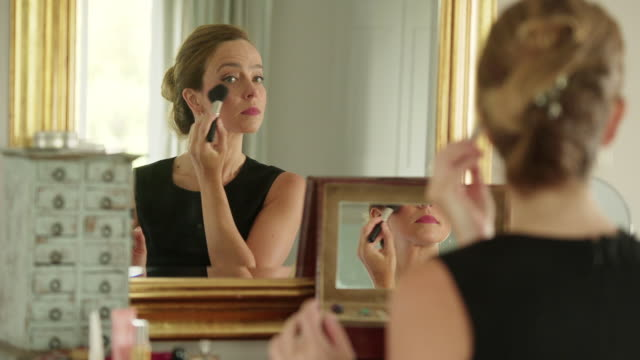 Make up for profession. Stock video clip of a woman in her 30s 40s applying make up in the mirror before she goes out to work in the morning. She's clearly a professional person taking pride in her appearance. vanity stock videos & royalty-free footage