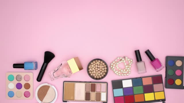 Make up products and accessories falling on pink background - Stop motion