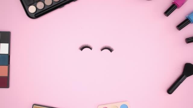 Make up products on pink background and eyelashes blinking - Stop motion