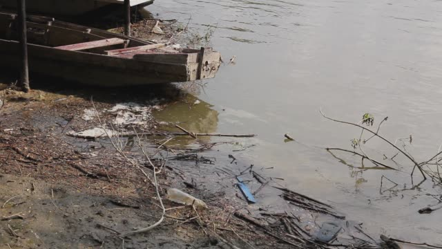 Makeshift pier on polluted river coast.