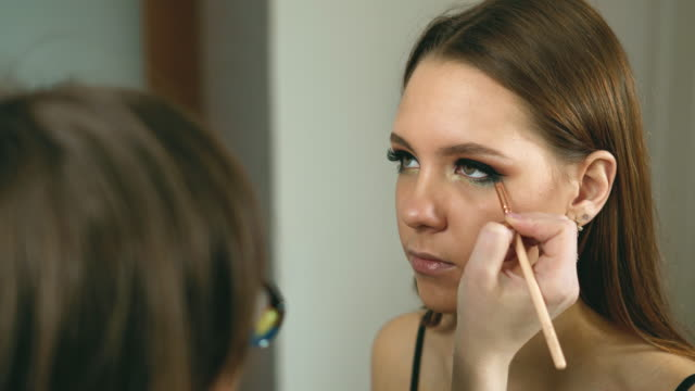 Makeup artist applies bright make-up on a girl who is preparing to get married.