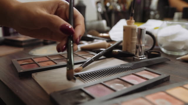 make-up artist applies eye shadow on background Professional make-up tools. A set of brushes, lipsticks, shadows, carcass make-up artist applies eye shadow on background Professional make-up tools. A set of brushes, lipsticks, shadows, carcass. eyeshadow stock videos & royalty-free footage