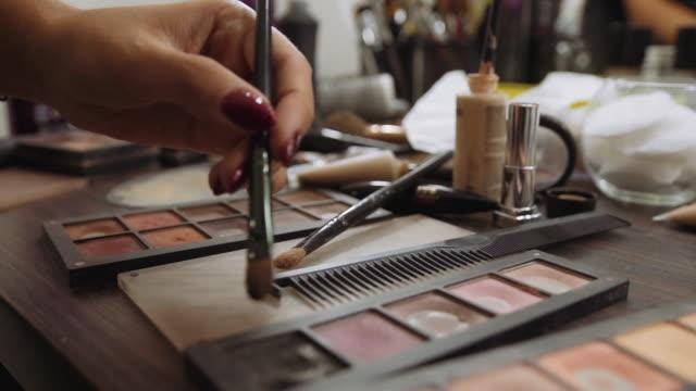 vidéos et rushes de maquilleuse applique ombre à paupières sur les outils de maquillage professionnel de fond. un ensemble de brosses, rouges à lèvres, ombres, carcasse - fard à paupières