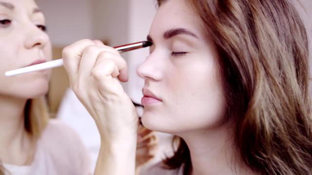 vidéos et rushes de artiste maquilleur s'applique l'ombre des yeux - pinceau à maquillage