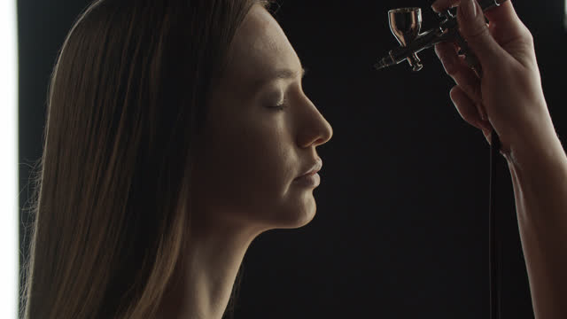 Make-up artist applies foundation to a girl face using an airbrush. Side view. video