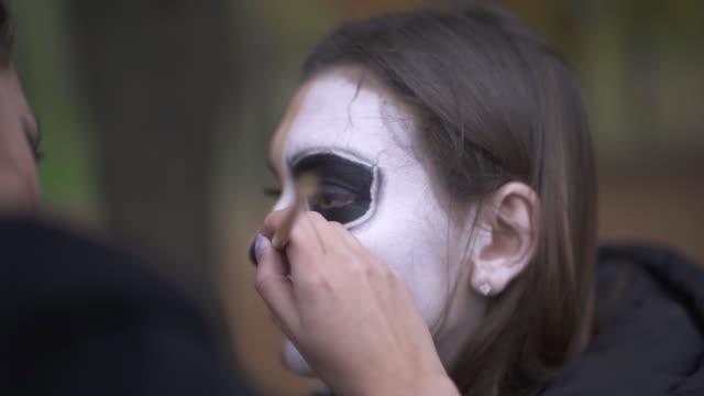 Makeup artist applies make-up to girl face. Halloween holiday.