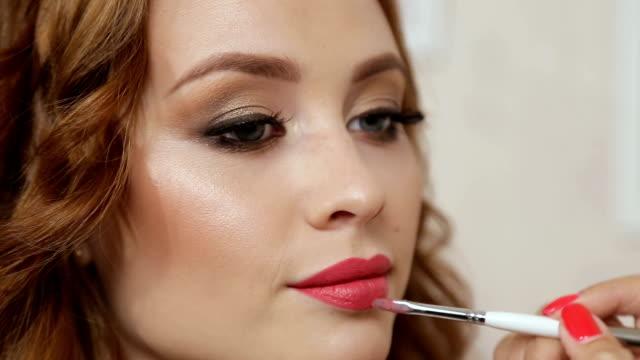 stockvideo's en b-roll-footage met visagist geldt rode lippenstift. mooie vrouw gezicht. hand van de meester, schilderij make-up lippen van jonge schoonheid model meisje. make-up in proces - mascara