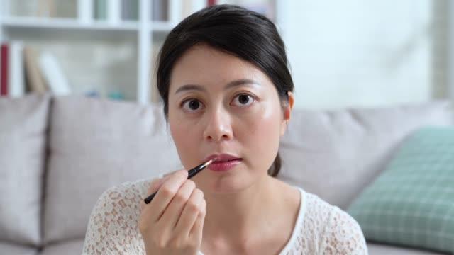 Makeup artist applies red pink lipstick
