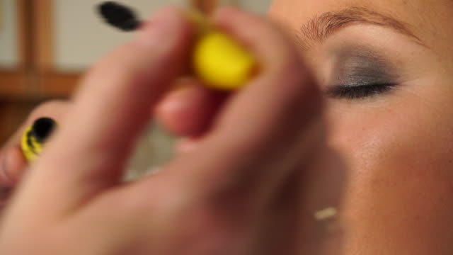 stockvideo's en b-roll-footage met visagist toepassing van zwarte mascara voor model oog 4k - ooglid