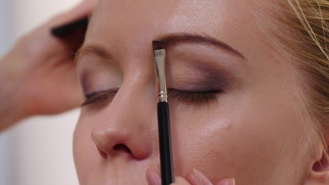 makeup artist applying brown color to female eyebrow - wschodnio europejski filmów i materiałów b-roll