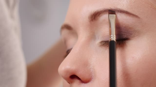 Makeup artist applying brown mascara to model eye video
