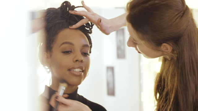 Makeup artist applying cosmetic powder with brush on woman face in beauty saloon video