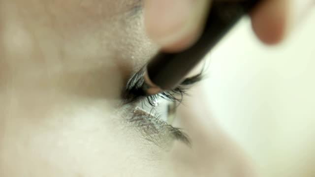 Makeup artist applying eyeliner on eyelid. video