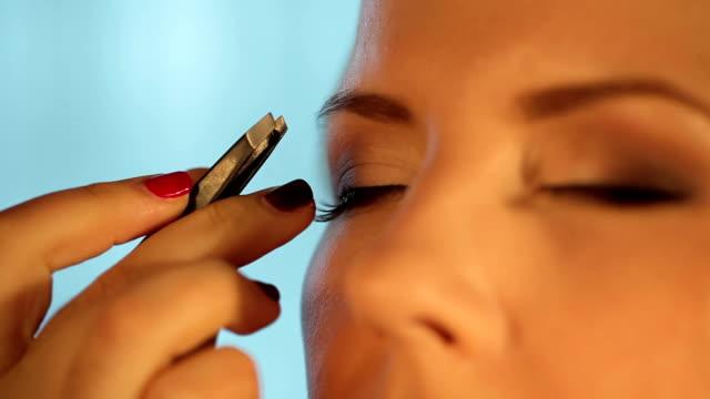 Makeup artist applying false eyelashes to model's eyes video