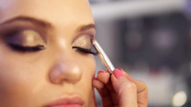 Make-up artist applying golden eye shadow makeup to the model's eyes. Close up view video