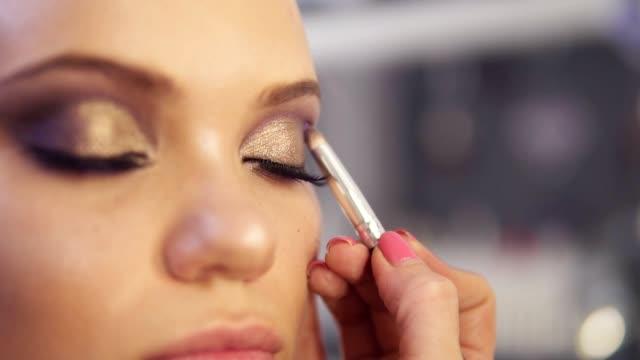 make-up artist tillämpa gyllene ögonskugga smink till modellens ögon. nära håll view - makeup artist bildbanksvideor och videomaterial från bakom kulisserna
