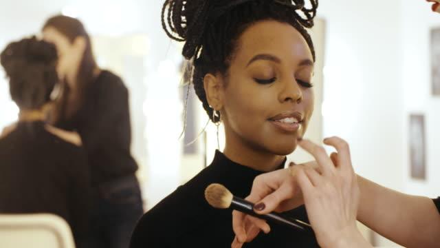 Makeup artist applying liquid highlighter for sculpting cheekbones on face model video