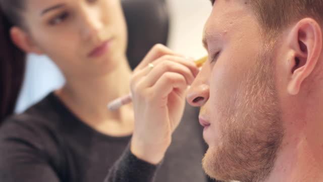 make-up artist ansöker make-up på young man ' s face - makeup artist bildbanksvideor och videomaterial från bakom kulisserna