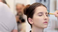 istock Make-up Artist Applying Make-up to a Young Adult Woman 1159773809