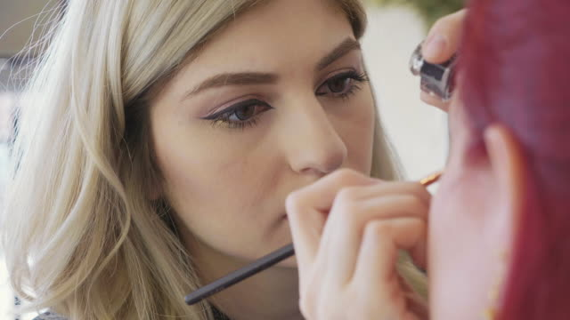 Make-up artist applying makeup to model's eye. Close up view. Portrait of young beautiful make-up artist applying make-up to model's eye. Redhead model at make up procedure, close up view. beautician stock videos & royalty-free footage