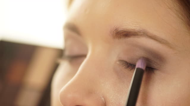 stockvideo's en b-roll-footage met visagist toepassen met borstel oogschaduw op vrouwelijke ogen 4k - toneelschmink