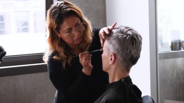 makeup artist brushing eyebrows of female model with short grey hair - kosmetyczka praca w salonie piękności filmów i materiałów b-roll