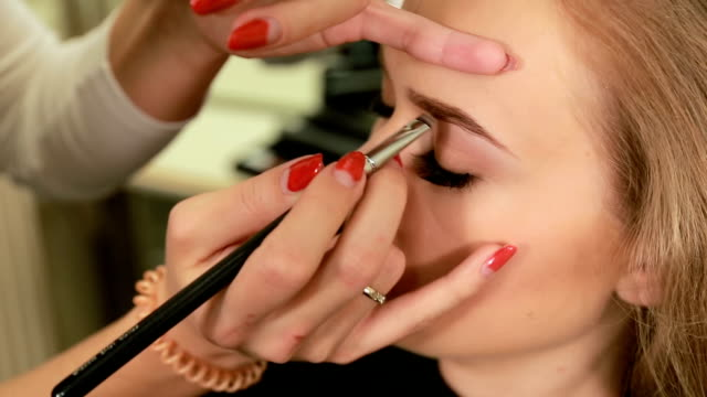 vídeos de stock, filmes e b-roll de maquiador fazendo maquiagem de uma menina loira linda jovem modelo, sharping sobrancelhas com um pincel - estilo de cabelo