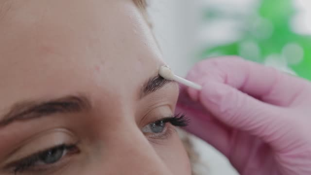 makeup artist lubricates the eyebrows of the client with gel before the procedure - ресницы стоковые видео и кадры b-roll