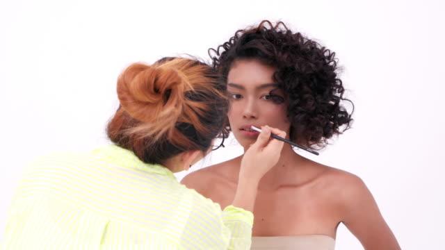 makeupartist gör kvinnan makeup - makeup artist bildbanksvideor och videomaterial från bakom kulisserna
