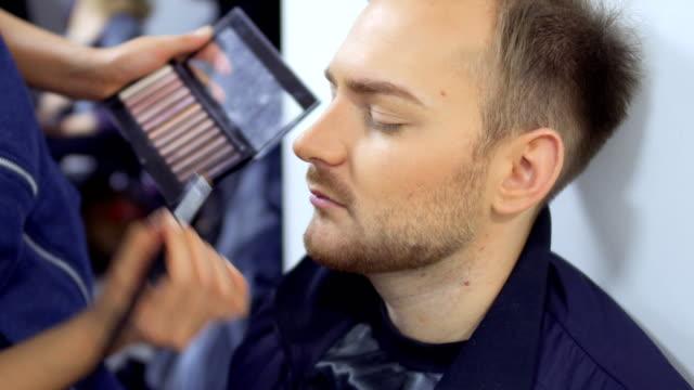 stockvideo's en b-roll-footage met visagist schildert baard van de man - vetschmink