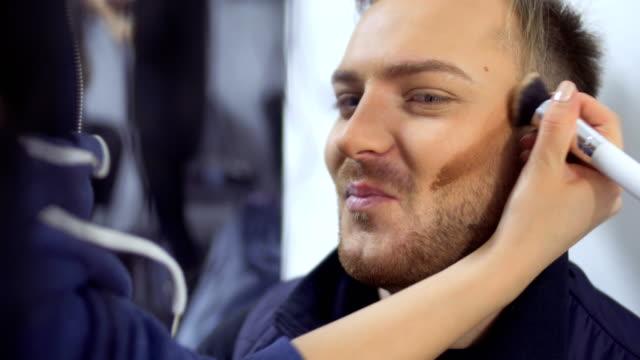 stockvideo's en b-roll-footage met visagist schildert wangen van jonge man - vetschmink
