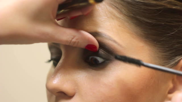 makeup artist paints the woman's eyes Makeup artist deals makeup on the model's face. She paints the shadows of the upper eyelids model. eyeliner stock videos & royalty-free footage