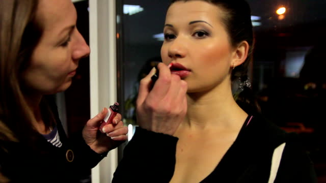 Make-up artist preparing model for fashion shoot, beauty contest backstage video