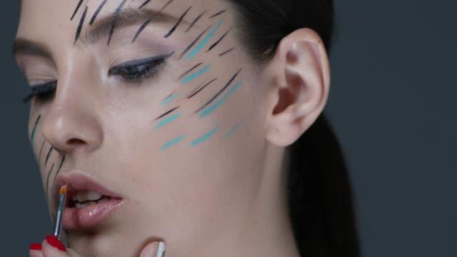メイクアップ アーティストは、モデルの顔にメイクを置きます。舞台裏。ファッションのビデオ。 - グリースペイント点の映像素材/bロール