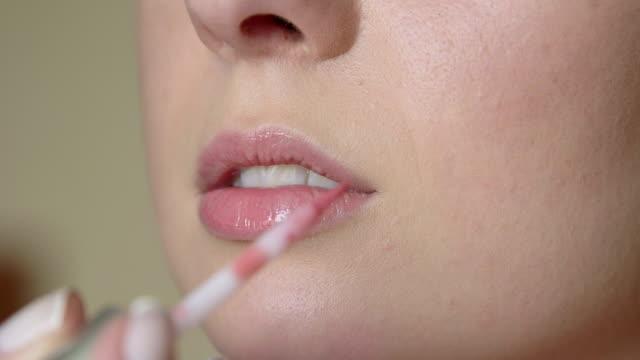 Makeup artist putting on lip gloss video